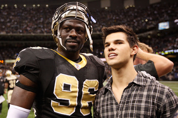 NEW ORLEANS, LA - DECEMBER 12:  Actor Taylor Lautner talks with Alex Brown #96 of the New Orleans Saints during the game against the St. Louis Rams at the Louisiana Superdome on December 12, 2010 in New Orleans, Louisiana.  (Photo by Chris Graythen/Getty