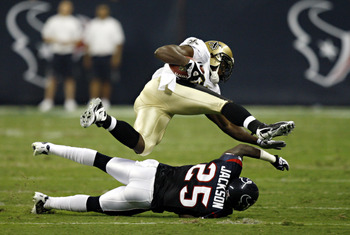 HOUSTON - AUGUST 20:  Running back Chris Taylor #36 of the New Orleans Saints is tripped up by cornerback Kareem Jackson #25 of the Houston Texans at Reliant Stadium on August 20, 2011 in Houston, Texas.  (Photo by Bob Levey/Getty Images)