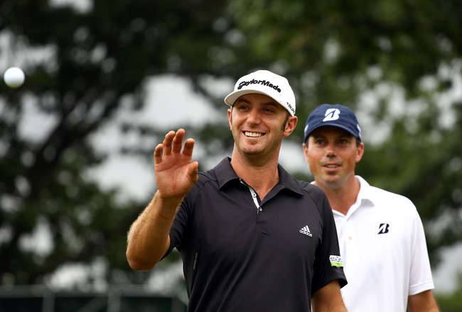 EDISON, NJ - AUGUST 27:  (L-R) Dustin Johnson catches a ball on the 18th green as Matt Kuchar looks on in the background during the third and final round of The Barclays at Plainfield Country Club on August 27, 2011 in Edison, New Jersey. The tournament w