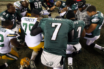 PHILADELPHIA, PA - JANUARY 09:  Michael Vick #7 of the Philadelphia Eagles, teammates and players of the Green Bay Packers pray together after their 2011 NFC wild card playoff game at Lincoln Financial Field on January 9, 2011 in Philadelphia, Pennsylvani