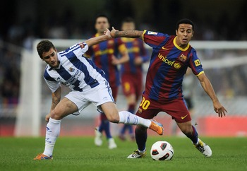 SAN SEBASTIAN, SPAIN - APRIL 30:  Thiago of FC Barcelona (R) fights for the ball against Antoine Griezmann of Real Sociedad during the La Liga match between Real Sociedad and Barcelona at Estadio Anoeta on April 30, 2011 in San Sebastian, Spain. Real Soci