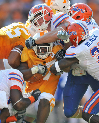 KNOXVILLE, TN - SEPTEMBER 18:  The Florida Gators defense smothers David Oku #27 of the Tennessee Volunteers at Neyland Stadium on September 18, 2010 in Knoxville, Tennessee.  (Photo by Grant Halverson/Getty Images)