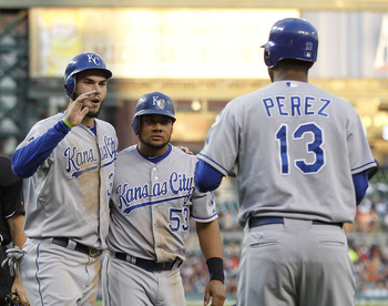 DETROIT - AUGUST 29:  Eric Hosmer #35 and Melky Cabrera #53 of the Kansas City Royals score on Johnny Giavotella #9 double to left field in the third inning and are congratulated by teammate Salvador Perez #13 during the game against the Detroit Tigers at