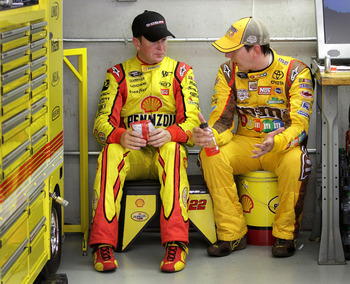 INDIANAPOLIS, IN - JULY 29:  Kurt Busch (L), driver of the #22 Shell/Pennzoil Dodge, talks with his brother, Kyle Busch (R), driver of the #18 M&M's Toyota, during practice for the NASCAR Sprint Cup Series Brickyard 400 at Indianapolis Motor Speedway on J