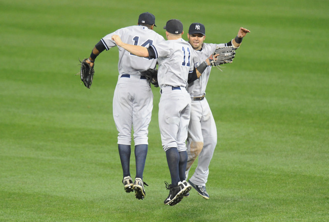 BALTIMORE, MD - AUGUST 28:  Curtis Granderson #14, Brett Gardner #11 and Nick Swisher #33 of the New York Yankees celebrate a win after a baseball game against the Baltimore Orioles at Oriole Park at Camden Yards on August 28, 2011 in Baltimore, Maryland.