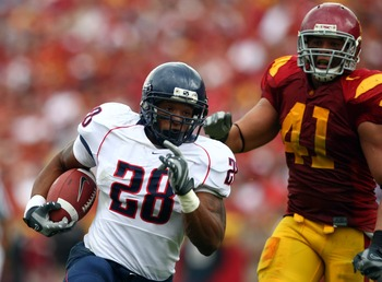 LOS ANGELES, CA - OCTOBER 13: Chris Jennings #28 of the Arizona Wildcats runs with the ball as Thomas Williams #41 of the USC Trojans chases during the first half of their Pac-10 Conference Game at the Los Angeles Memorial Coliseum October 13, 2007 in Los