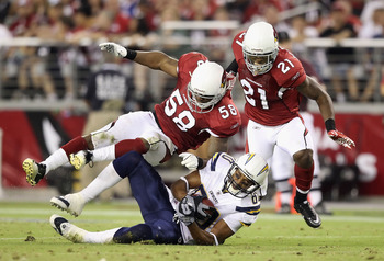 GLENDALE, AZ - AUGUST 27:  Wide receiver Malcom Floyd #80 of the San Diego Chargers is hit by linebacker Daryl Washington #58 and cornerback Patrick Peterson #21 of the Arizona Cardinals after a reception during the preseason NFL game at the University of