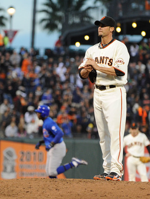 SAN FRANCISCO, CA - AUGUST 30: Ryan Vogelsong #32 of the San Francisco Giants rubs up a new baseball as Alfonso Soriano #12 of the Chicago Cubs trots around the bases after hitting a home run in the second inning during a MLB baseball game at AT&T Park on
