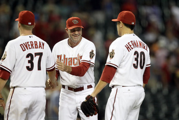 PHOENIX, AZ - AUGUST 30:  Manager Kirk Gibson (C) of the Arizona Diamondbacks high fives Lyle Overbay #37 and David Hernandez #30 after defeating the Colorado Rockies in the Major League Baseball game at Chase Field on August 30, 2011 in Phoenix, Arizona.