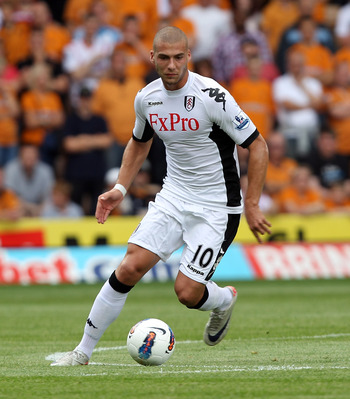 WOLVERHAMPTON, ENGLAND - AUGUST 21:  Pajtim Kasami of Fulham is challenged by of Wolves during the Barclays Premier League match between Wolverhampton Wanderers and Fulham at Molineux on August 21, 2011 in Wolverhampton, England.  (Photo by Ross Kinnaird/