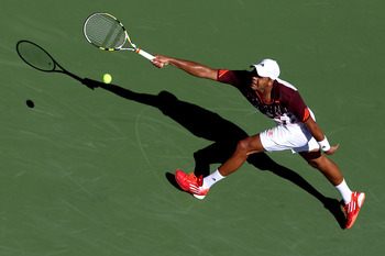 NEW YORK, NY - AUGUST 30:  Jo-Wilfried Tsonga of France returns a shot against Yen-Hsun Lu of Taiwan during Day Two of the 2011 US Open at the USTA Billie Jean King National Tennis Center on August 30, 2011 in the Flushing neighborhood of the Queens borou