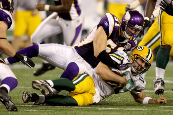 MINNEAPOLIS - NOVEMBER 21:  Quarterback Aaron Rodgers #12 of the Green Bay Packers is hit by Ben Leber #51 of the Minnesota Vikings after being chased from the pocket at the Hubert H. Humphrey Metrodome on November 21, 2010 in Minneapolis, Minnesota.  (Ph