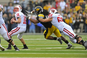 IOWA CITY, IA - OCTOBER 23- Quarterback Scott Tolzien #16 of the Wisconsin Badgers throws under pressure from Defensive lineman Adrian Clayborn #94 of the University of Iowa Hawkeyes as offensive lineman Gabe Carimi #68 defends during the first half of pl