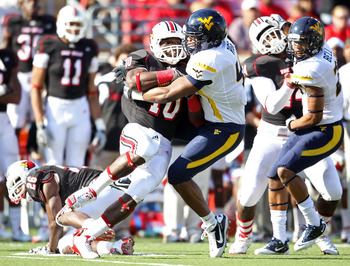LOUISVILLE, KY - NOVEMBER 20:  Dominique Brown #10 of the Louisville Cardinals is tackled by Doug Rigg #47 of the West Virginia Mountaineers during the game at Papa John's Cardinal Stadium on November 20, 2010 in Louisville, Kentucky.  (Photo by Andy Lyon