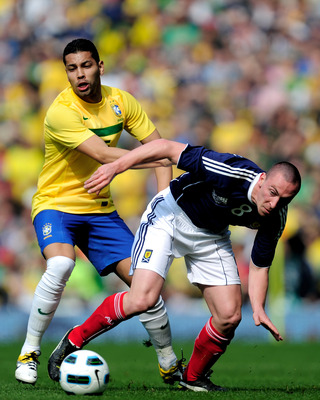 LONDON, ENGLAND - MARCH 27:  Andre Santos of Brazil tackles Scott Brown of Scotland during the International friendly match between Brazil and Scotland at Emirates Stadium on March 27, 2011 in London, England.  (Photo by Jamie McDonald/Getty Images)