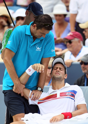 MASON, OH - AUGUST 21:  Novak Djokovic of Serbia is treated by ATP trainer Hugo Gravil during the Western & Southern Open at the Lindner Family Tennis Center on August 21, 2011 in Mason, Ohio.  (Photo by Elsa/Getty Images)