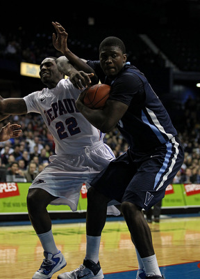 ROSEMONT, IL - FEBRUARY 19: Mouphtaou Yarou #13 of the Villanova Wildcats grabs a rebound under pressure from Tony Freeland #22 of the DePaul Blue Demons at the Allstate Arena on February 19, 2011 in Rosemont, Illinois. Villanova defeated DePaul 77-75 in