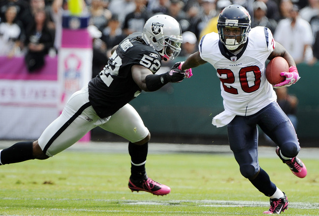 OAKLAND, CA - OCTOBER 3: Running back Steve Slaton #20 of the Houston Texans pushes away from linebacker Quentin Groves #52 of the Oakland Raiders during an NFL football game October 3, 2010 at The Oakland-Alameda County Coliseum in Oakland, California.