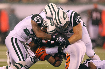 EAST RUTHERFORD, NJ - AUGUST 21:  Emanuel Cook #27,Brodney Pool #22, and Garrett McIntyre #50 of the New York Jets tackle Cedric Peerman #30 of the Cincinnati Bengals during their pre season game on August 21, 2011 at the New Meadowlands Stadium in East R