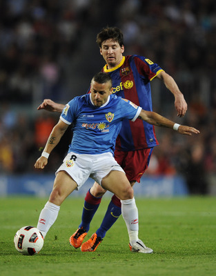 BARCELONA, SPAIN - APRIL 09:  Lionel Messi of FC Barcelona (R) fights for the ball againstAlbert Crusat Domene of Almeria during the La Liga match between FC Barcelona and UD Almeria at Camp Nou on April 9, 2011 in Barcelona, Spain.  (Photo by David Ramos