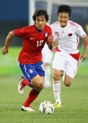 GUANGZHOU, CHINA - NOVEMBER 15:  Park Chu Young of South Korea completes the ball with Li Kai of China during a Men's 1/8 Final football match between South Korea and China during the 16th Asian Games Guangzhou 2010 at Tianhe Stadium on November 15, 2010