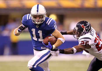 INDIANAPOLIS - NOVEMBER 01: Anthony Gonzalez #11 of Indianapolis Colts runs with the ball while defended by Eugene Wilson #26 of the Houston Texans during the NFL game at Lucas Oil Stadium on November 1, 2010 in Indianapolis, Indiana.  (Photo by Andy Lyon