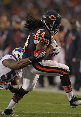 CHICAGO, IL - AUGUST 13:  Marion Barber #24 of the Chicago Bears runs for yardage as Antonio Coleman #59 of the Buffalo Bills closes in during a preseason game at Soldier Field on August 13, 2011 in Chicago, Illinois. The Bears defeated the Bills 10-3. (P
