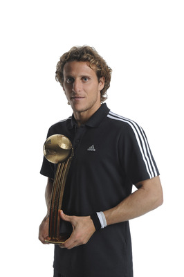 HERZOGENAURACH, GERMANY - DECEMBER 14:  Diego Forlan of Uruguay poses with the adidas Golden Ball Winner Trophy at the adidas HQ on December 14, 2010 in Herzogenaurach, Germany.  (Photo by Getty Images for adidas)