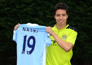 MANCHESTER, ENGLAND - AUGUST 26:  Samir Nasri of Manchester City holds his playing shirt during a photocall at Carrington training ground on August 26, 2011 in Manchester, England.  (Photo by Alex Livesey/Getty Images)