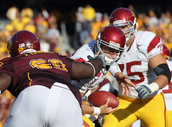 MINNEAPOLIS - SEPTEMBER 18:  Jewhan Edwards #68 of the Minnesota Golden Gophers grabs the facemask of quarterback Matt Barkley #7 of the USC Trojans during the game on September 18, 2010 at TCF Bank Stadium in Minneapolis, Minnesota.  (Photo by Jamie Squi
