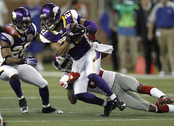 DETROIT, MI - DECEMBER 13:  Asher Allen #21 of the Minnesota Vikings tries to escape the tackle of Mario Manningham #82 of the New York Giants after a second quarter interception at Ford Field on December 13, 2010 in Detroit, Michigan.  (Photo by Gregory 