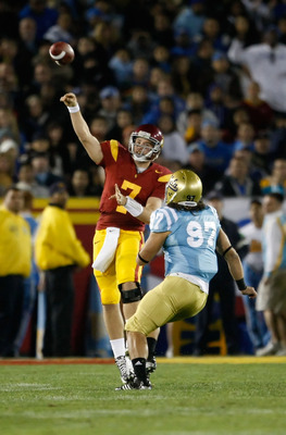 LOS ANGELES, CA - NOVEMBER 28:  Matt Barkley #7 of the USC Trojans throws the ball down field while being pursued by Damien Holmes #97 of the UCLA Bruins in the first half at the Los Angeles Memorial Coliseum on November 28, 2009 in Los Angeles, Californi