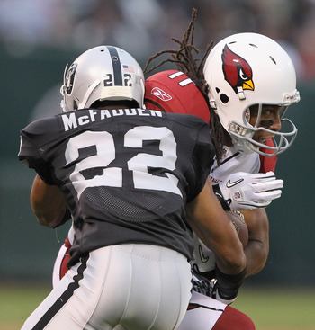 OAKLAND, CA - AUGUST 11:  Larry Fitzgerald #11 of the Arizona Cardinals is hit by Walter McFadden #22 of the Oakland Raiders at O.co Coliseum on August 11, 2011 in Oakland, California.  (Photo by Ezra Shaw/Getty Images)