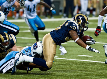 ST. LOUIS, MO - AUGUST 20: Jerious Norwood #34 of the St. Louis Rams rushes for a gain and is tackled by Rennie Curran #53 of the Tennessee Titans at the Edward Jones Dome on August 20, 2011 in St. Louis, Missouri.  (Photo by Ed Szczepanski/Getty Images)