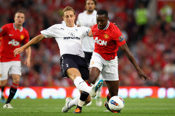 MANCHESTER, ENGLAND - AUGUST 22:  Michael Dawson of Tottenham Hotspur tackles Danny Welbeck of Manchester United during the Barclays Premier League match between Manchester United and Tottenham Hotspur at Old Trafford on August 22, 2011 in Manchester, Eng