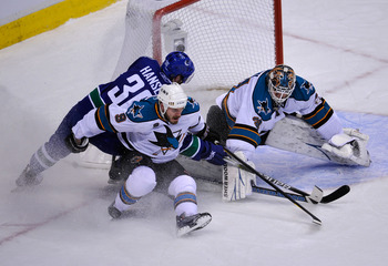 VANCOUVER, CANADA - MAY 18:  Jannik Hansen #36 of the Vancouver Canucks skates to the net as Ian White #9 of the San Jose Sharks falls backwards trying to defend the play in Game Two of the Western Conference Finals during the 2011 Stanley Cup Playoffs at