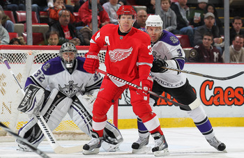 DETROIT, MI - MARCH 9:  Kris Draper #33 of the Detroit Red Wings stands between Jonathan Quick #32 and Jack Johnson #3 of the Los Angeles Kings waiting to deflect a shot in a game on March 9, 2011 at the Joe Louis Arena in Detroit, Michigan. The Kings def