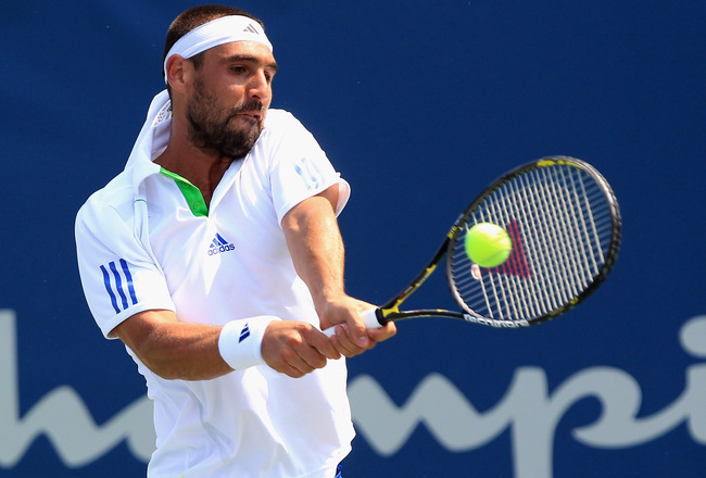 WINSTON-SALEM, NC - AUGUST 25:  Marcos Baghdatis of Cyprus returns a shot to John Isner of the USA during the Winston-Salem Open at the Wake Forest University Tennis Complex on August 25, 2011 in Winston-Salem, North Carolina.  (Photo by Streeter Lecka/Ge