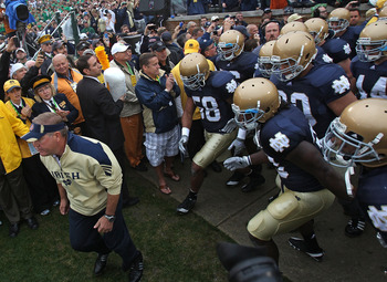 SOUTH BEND, IN - SEPTEMBER 11: Head coach Brian Kelly of the Notre Dame Fighting Irish (L) leads his team onto the field before a game against the Michigan Wolverines at Notre Dame Stadium on September 11, 2010 in South Bend, Indiana. Michigan defeated No
