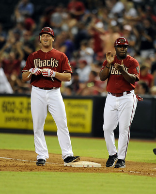 PHOENIX, AZ - AUGUST 31:  First Base Coach Eric Young #7 of the Arizona Diamondbacks congratulates Sean Burroughs #11 as he smiles at the bench after getting a pinch hit against the Colorado Rockies at Chase Field on August 31, 2011 in Phoenix, Arizona.