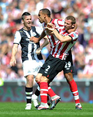 SUNDERLAND, ENGLAND - AUGUST 20:  Anton Ferdinand of Sunderland pulls team-mate Phil Bardsley away from Joey Barton of Newcastle United during the Barclays Premier League match between Sunderland and Newcastle United at Stadium of Light on August 20, 2011