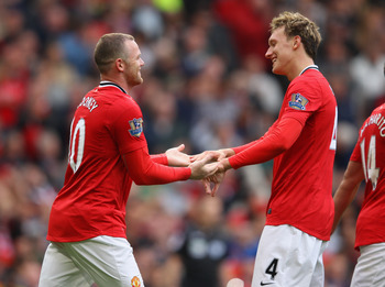 MANCHESTER, ENGLAND - AUGUST 28:  Wayne Rooney of Manchester United celebrates with Phil Jones after scoring his third goal from the penalty spot during the Barclays Premier League match between Manchester United and Arsenal at Old Trafford on August 28,