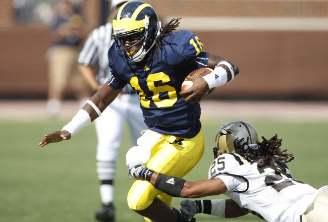 ANN ARBOR, MI - SEPTEMBER 5:  Denard Robinson #16 of the Michigan Wolverines carries the ball against David Lewis #26 of the Western Michigan Broncos during the game on September 5, 2009 at Michigan Stadium in Ann Arbor, Michigan. (Photo by Gregory Shamus