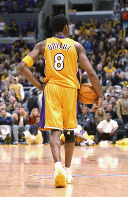LOS ANGELES - JANUARY 16:  Guard Kobe Bryant #8 of the Los Angeles Lakers walks the ball downcourt as he waits for play to begin during the NBA game against the Miami Heat at the Staples Center in Los Angeles, California on January 16, 2002.  The Heat def