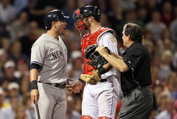 BOSTON, MA - AUGUST 30:  Francisco Cervelli #17 of the New York Yankees reacts after he is hit by a pitch as catcher Jarrod Saltalamacchia #39 of the Boston Red Sox and home plate umpire Ed Rapuano try to calm Cervelli down on August 30, 2011 at Fenway Pa