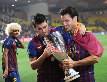 MONACO - AUGUST 26: David Villa (L) and Cesc Fabregas of FC Barcelona celebrate with the trophy during as Daniel Alves walks in the background during the UEFA Super Cup match between FC Barcelona and FC Porto at Louis II Stadium on August 26, 2011 in Mona