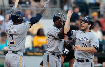 PITTSBURGH - AUGUST 22: George Kottaras #16 of the Milwaukee Brewers celebrates with teammates Yuniesky Betancourt #3 and Nyjer Morgan #2 after scoring against the Pittsburgh Pirates in the 4th inning during the game on August 22, 2011 at PNC Park in Pitt