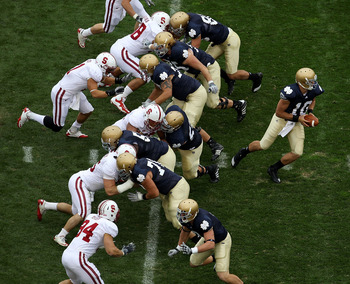 SOUTH BEND, IN - SEPTEMBER 25: Dayne Crist #10 of the Notre Dame Fighting Irish turns to hand-off as his offensive line blocks against the Stanford Cardinal defense at Notre Dame Stadium on September 25, 2010 in South Bend, Indiana. Standford defeated Not