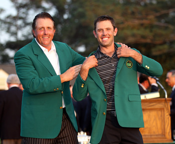 AUGUSTA, GA - APRIL 10:  Charl Schwartzel of South Africa is presented with his Green Jacket by Phil Mickelson for winning the Masters after the final round of the 2011 Masters Tournament at Augusta National Golf Club on April 10, 2011 in Augusta, Georgia
