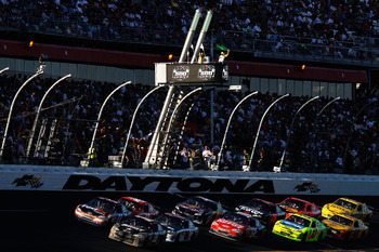 DAYTONA BEACH, FL - FEBRUARY 20:  Ryan Newman, driver of the #39 U.S. Army Chevrolet, and Denny Hamlin, driver of the #11 FedEx Toyota, lead a pack of cars past the green flag for a restart during the NASCAR Sprint Cup Series Daytona 500 at Daytona Intern